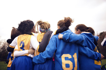 Soccer players in huddle during match against clear sky