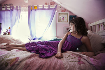 Girl in purple dress resting on bed at home on sunny day