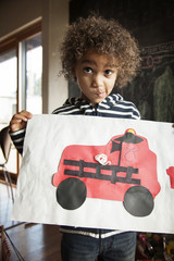 Boy showing his art work of fire engine