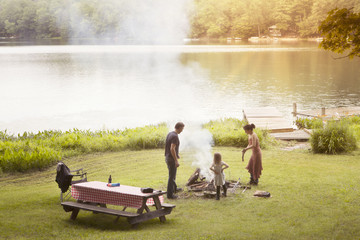 Family preparing campfire on field