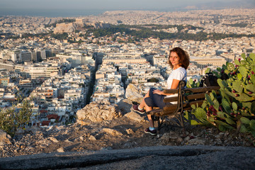 woman sitting on Lycabettus Hill, the highest point in the city overlooking Athens with the Acropolis - world traveller