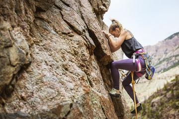 Side view of hiker climbing mountain