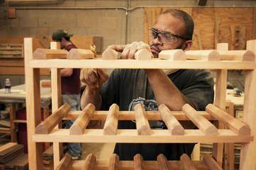 Serious manual worker carving wooden furniture at workshop
