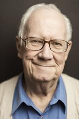 Portrait of smiling senior man standing against wall