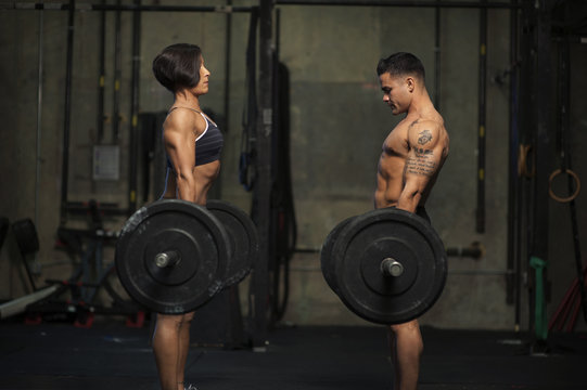 Side view of man and woman exercising with barbells