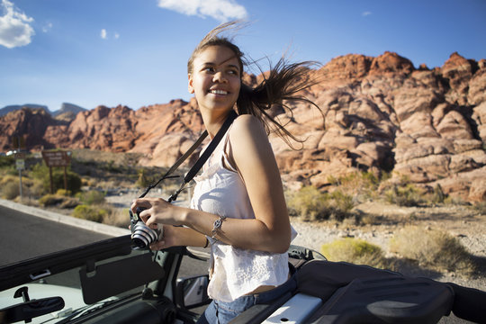 Smiling woman with camera standing in car
