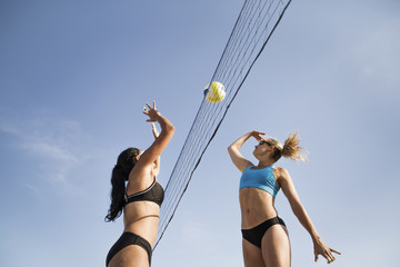 Low angle view of female friends playing volleyball against sky
