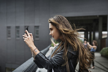 Side view of woman taking pictures with phone