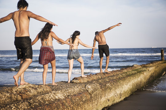 Rear view of couples walking on groyne wall at beach