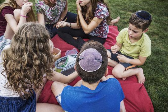 High angle view of family enjoying during picnic at park