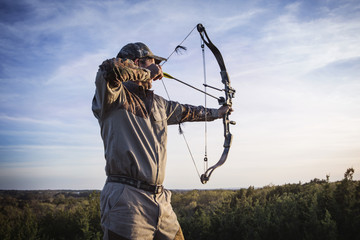 Hunter aiming with bow and arrow while standing on field against sky