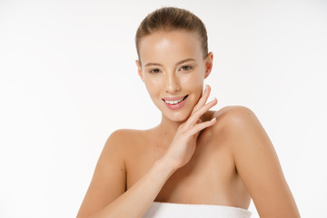 Beautiful young woman with clean fresh perfect skin. Portrait of model with natural nude make up, with towel on the body. Facial treatment. Cosmetology, beauty and spa. Skin care.
