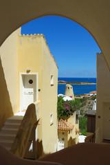 Nice view through arch with typical house, blue sky and Mediterranean Sea, Porto Cervo, Sardinia