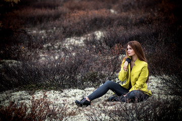 Woman sitting in the dry black bushes