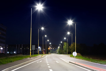 night empty road with modern LED street lights, entrance to a small town Fotomurales