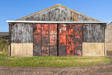 Old barn with metal doors, rusty and red