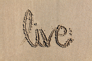 The word 'live' written in sand on a beach