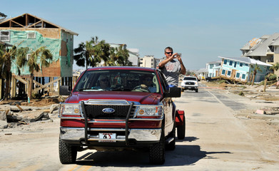 A passenger shoots video as a truck drives along U.S. Highway 98 in the aftermath of Hurricane Michael at Mexico Beach