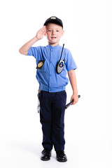 Cute little police boy with smile on face and gun on white background. Intelligent cool children in police suit with blue eyes and weapon. salute