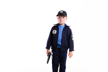 Cute sad little police boy with smile on face and gun on white background. Intelligent cool children in police suit with blue eyes and weapon