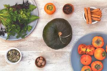 Green Pumpkin, persimmons and ingredients for tasty vegetarian cooking on light wooden surface