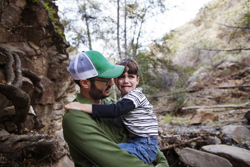 Father consoling upset son while carrying in forest
