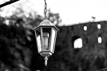 Vintage street lamp full of flies hanging on a chain. Black and white image Fotomurales