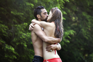 Couple embracing while kissing in forest