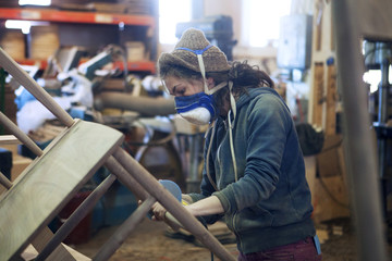 Carpenter sanding wooden chair at workshop