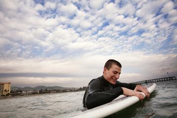 Man holding surfboard in sea, California, USA