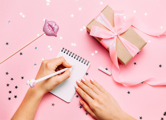 Beautiful female hands with trendy manicure writing in notebook