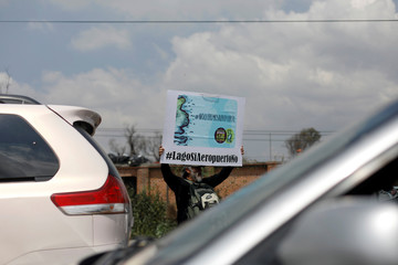 "A member of civil organisation holds a sign reading ""We do not want an airport. Lake yes, airport no"" during an occupation of toll booths, allowing the free access to motorway in protest against the construction of the new Mexico City international airport"