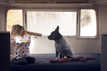 Girl looking at dog through cardboard tube while kneeling on bed in vehicle