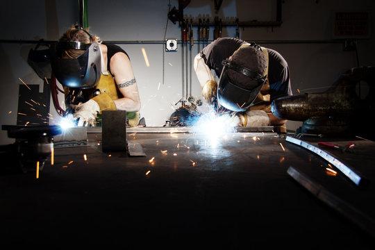 Workers welding in factory
