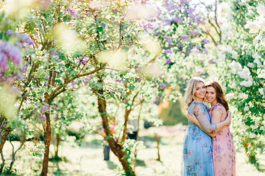 Adorable happy cheerful fabulous twin sisters in different beautiful summer dresses posing outdoor.  Similar cute female models in lilac colorful bushes with bloming flowers in park portrait.  Family.