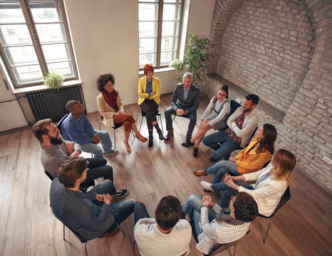 business people sitting at circle in board room and discussing.