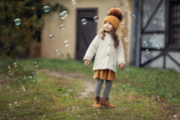 girl playing with soap bubbles outdoors Wall mural