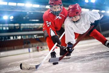 children hockey player handling puck on ice.