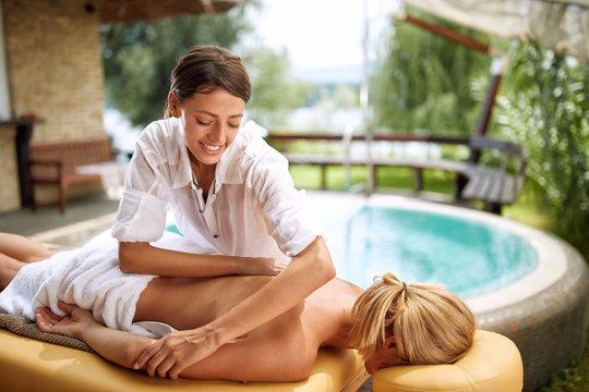 Massage therapist doing a back massage on outdoor.