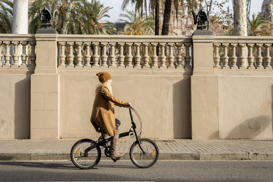 Woman in hat and coat riding a bike along sunny road.