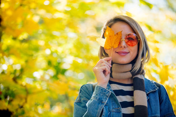 Young beautiful blonde girl in blue jeans clothes have rest in the park in autumn season time.