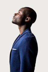 Profile portrait of young black man looking up against a white b