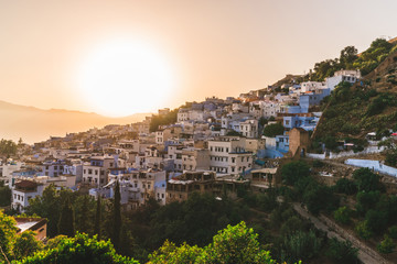 Amazing Chefchaouen panorama, blue city skyline on the hill, Morocco during sunset big red orange sun