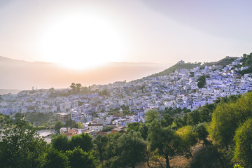 Panorama of Chefchaouen, Morocco at golden hour before sunset. Town famous by the blue painted walls of the houses - amazing sunset purple sky