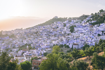 Panorama of Chefchaouen, Morocco at golden hour before sunset. Town famous by the blue painted walls of the houses - amazing sunset purple orange sky