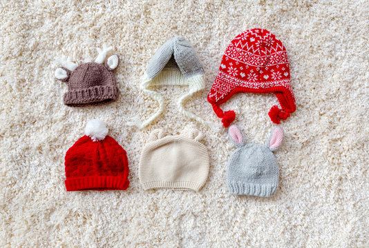 Assorted winter style knitted hats on a white carpet
