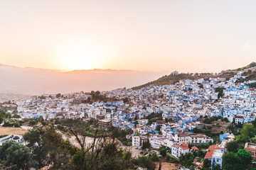 Panorama night city of Chefchaouen Morocco during sunset with orange sky. Blue city in night lights with sun behind mountains. Journey through Morocco, magical place.