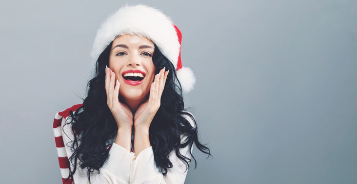 Happy woman with a Santa hat on a gray background