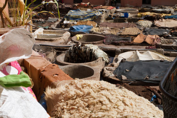 moroccan men traditionally stacking dyed garments at a leather tannery in a moroccan residential neighborhood