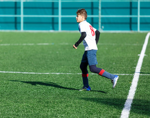 football teams - boys in red, blue, white uniform play soccer on the green field. boys dribbling. dribbling skills. Team game, training, active lifestyle, hobby, sport for kids concept